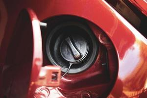 La porte du réservoir de carburant est ouverte et le bouchon du réservoir de carburant fermé sur la voiture rouge photo