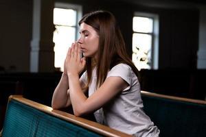 Une fille chrétienne en chemise blanche est assise et prie avec un cœur humble dans l'église photo