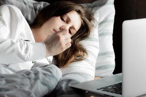 jeune fille mignonne sur une journée ensoleillée en regardant un ordinateur portable photo