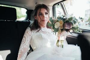photo de mariage de la mariée assise dans la voiture avec un bouquet de fleurs