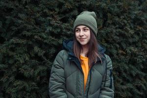 Portrait d'une belle jeune fille souriante près d'un arbre de Noël en plein air photo