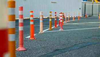 Poteau de signalisation orange sur route goudronnée en stationnement photo