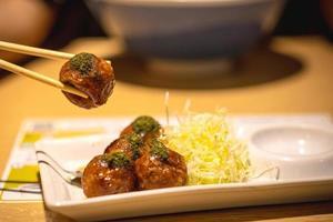Gros plan de takoyaki, baguettes serrées sur boule de takoyaki sur fond de table en bois photo