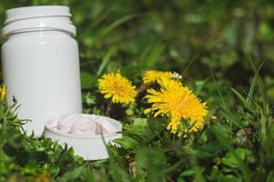 pilules blanches dans l'herbe avec des fleurs photo