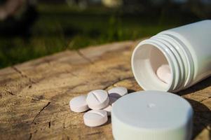 pot blanc et pilules blanches reposent sur une souche photo