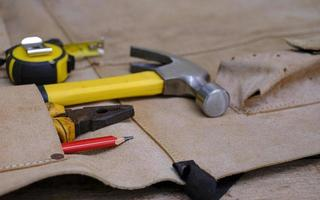 Collection d'outils à main vieux bois en tablier en cuir sur un établi en bois rugueux photo