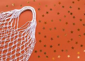 Blanc, chaîne, coton, éco, sac, sur, arrière-plan orange, à, or, étoiles, décoration, simple, plat, poser, à, copie, espace, écologie, zéro déchet, concept Banques de Photographies photo