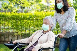 Aidez une vieille dame asiatique âgée ou âgée en fauteuil roulant électrique et portant un masque facial pour protéger l'infection de sécurité coronavirus Covid 19 dans le parc photo