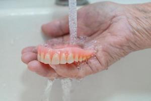 Senior asiatique ou vieille femme âgée patient tenant une prothèse partielle de dents de remplacement photo