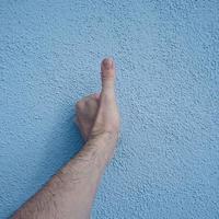 main faisant des gestes sur le mur bleu photo