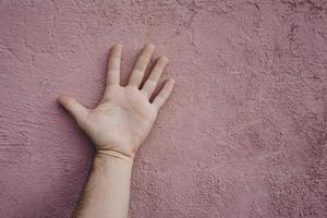 main faisant des gestes sur le mur rose photo