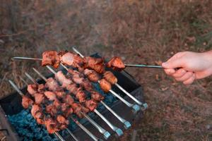 Homme friture shish kebab sur le gril photo