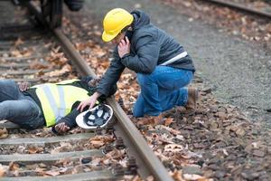 Ingénieur ferroviaire afro-américain blessé dans un accident du travail sur la voie ferrée son collègue en utilisant son téléphone portable pour appeler le 911 photo