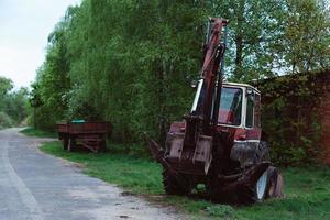 Vieux tracteur rouillé rouge dans un champ près de la route photo