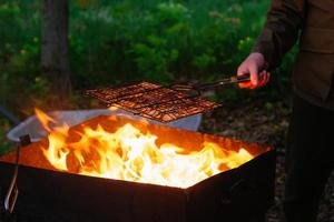 Une main d'homme tient un gril en fer avec une brochette de saucisse sur le feu photo