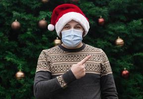 Portrait en gros plan d'un homme portant un chapeau de père Noël et un masque médical photo