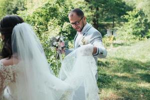 Marié barbu dans une veste grise et des lunettes tenant un voile ou une robe de mariée de la mariée photo
