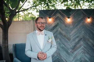 photo de mariage des émotions d'un marié barbu avec des lunettes dans une veste grise et un style rustique