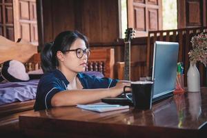 Jeune femme travaillant assis sur un canapé avec un ordinateur portable à la maison photo