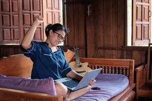 Une femme accomplie heureuse travaillant en ligne avec une tablette numérique alors qu'elle était assise à la maison photo