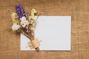 une carte blanche décorée de bouquet de fleurs séchées multicolores sur le tissu marron photo