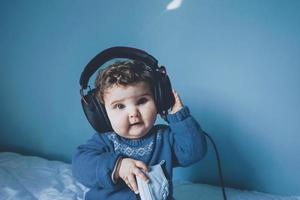 petit bébé jouant avec ses écouteurs papa photo