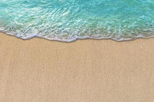 Été avec vague turquoise dans les vagues douces de plage tropicale avec de la mousse de l'océan bleu sur la plage de sable photo