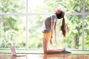 apprentissage en ligne yoga sur internet personne mode de vie exercice en salle à la maison fitness sport entraînement pour femme en bonne santé femme heureux entraînement dans le salon à la maison yoga auto apprentissage relaxation photo