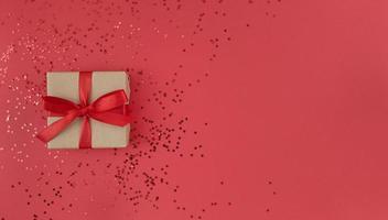 Coffret cadeau enveloppé dans un papier kraft avec ruban rouge avec un arc et des confettis sur fond rouge plat festif monochrome poser avec copie photo