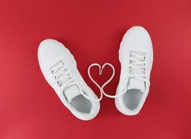 Chaussures de sport blanches et forme de coeur à partir de lacets sur un fond rouge simple pose à plat photo