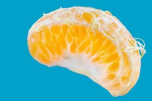 Tranche de mandarine fraîche unique sur fond bleu photo