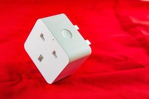 Prise de courant intelligente wifi de couleur blanche sur fond rouge photo