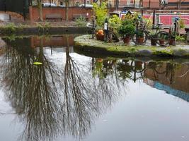 Scène atmosphérique de réflexions d'arbres dans le système de canaux victorien restauré à Castlefield Manchester photo