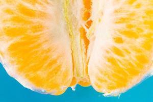 Tranches de mandarine fraîche sur fond bleu photo