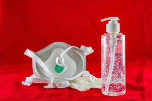 Gel désinfectant gants en latex blanc et masque sur le concept de protection rouge contre le virus de la pollution, la grippe et le coronavirus photo