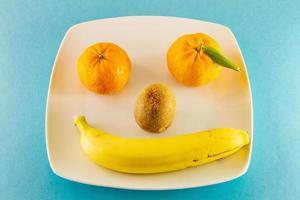 Kiwi mandarines et une banane sur une plaque blanche comme visage humain souriant photo