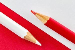 crayons de couleur sur papiers de couleur rouge et blanc disposés en diagonale photo