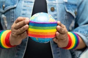 Dame asiatique tenant le drapeau de couleur arc-en-ciel avec symbole du globe du mois de la fierté lgbt célébrer annuel en juin social des droits de l'homme transgenres bisexuels lesbiennes photo