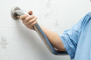 Senior asiatique ou âgée vieille dame femme patient utiliser la sécurité de la poignée de salle de bains de toilettes dans l'hôpital de soins infirmiers en bonne santé concept médical photo