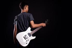 Jeune homme en veste de cuir noir avec guitare électrique sur fond noir en studio photo