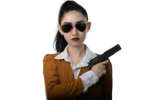 Portrait belle femme asiatique portant un costume jaune une main tenant le pistolet à fond blanc photo