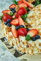 Gâteau meringuée aux fraises avec des pétales d'amande sur du papier journal photo