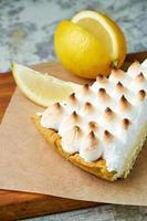 un morceau de tarte au citron décoré d'une tranche de citron sur une planche de bois photo