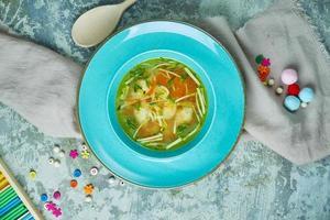 Soupe de poulet aux légumes verts dans une assiette bleue photo