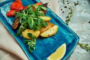légumes grillés et pommes de terre rustiques sur une plaque bleue photo