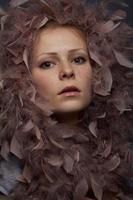 belle fille avec des plumes de boa et des taches de rousseur photo