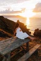 femme enceinte contre un paysage océanique au coucher du soleil photo