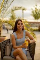 Jeune femme buvant du jus d'orange au café de la rue photo