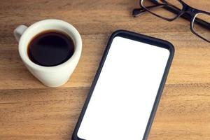 téléphone intelligent sur le bureau avec des lunettes à écran blanc et une tasse de café sur une table en bois maquette modèle photo