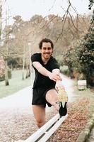 Un jeune homme qui s'étend ses jambes sur un banc d'un parc au cours d'une journée ensoleillée tout en souriant à la caméra photo